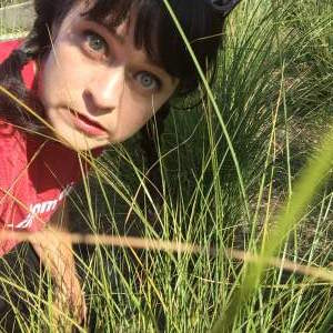 woman makes a silly face in tall grass