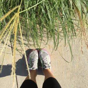 woman's sneakers on a sidewalk