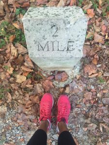 woman's feet standing in front of a 2 mile marker