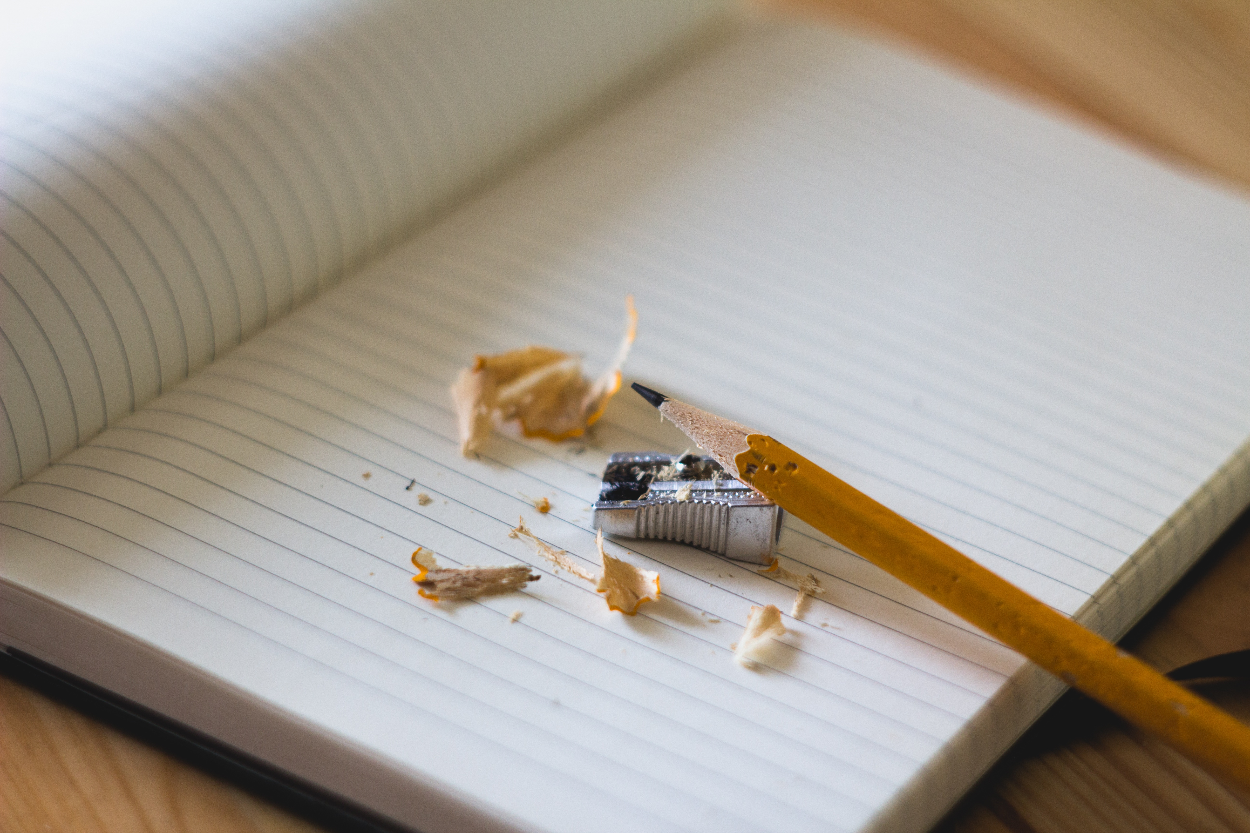 pencil laying on top of pencil shavings and a pencil sharpener on an open notebook at Infomedia's office